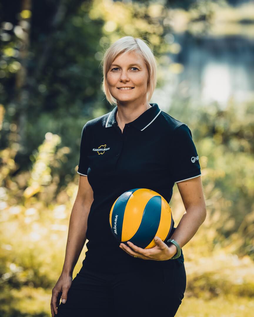 Kainuun Liikunta ry - Yhteystiedot - Ira Liuski - Nainen pitelee lentopalloa ja hymyilee kameralle.