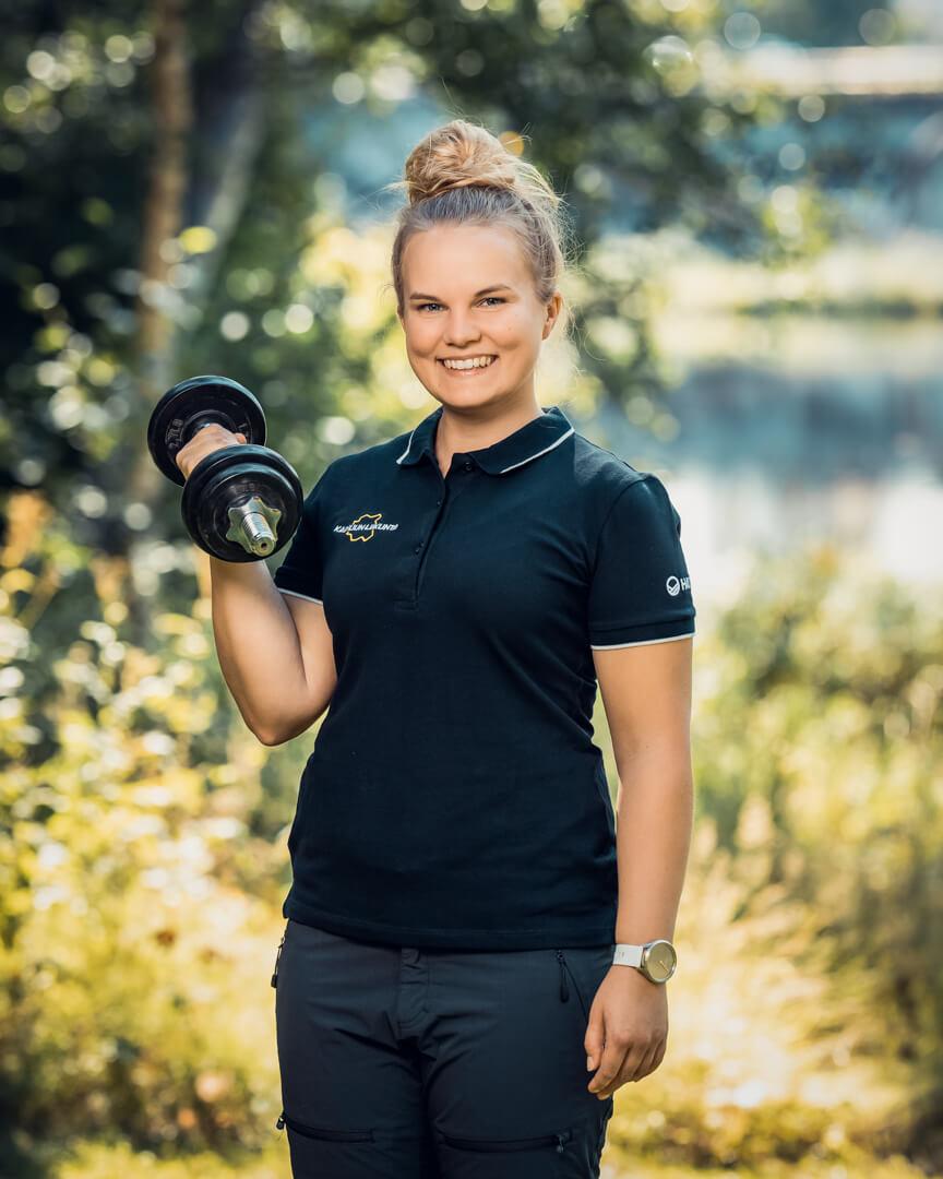 Kainuun Liikunta ry - Yhteystiedot - Anni Heikkinen - Nainen pitelee käsipainoa ja hymyilee kameralle.