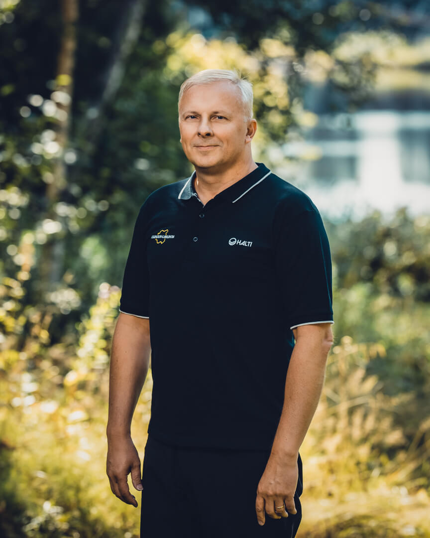 Kainuun Liikunta ry - Yhteystiedot - Timo Mannermaa - Mies seisoo metsässä ja hymyilee kameralle.