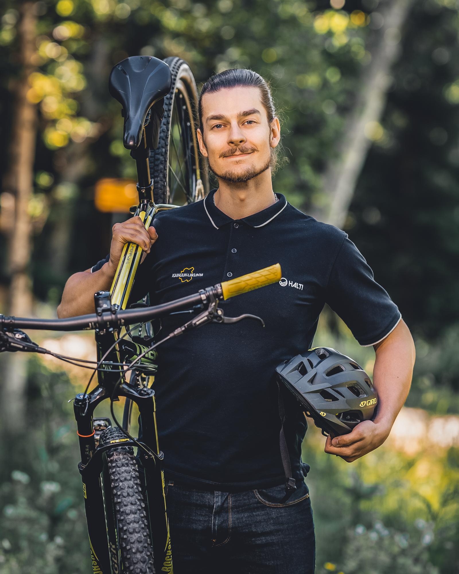 Kainuun Liikunta ry - Yhteystiedot - Tatu Heikkilä - Mies pitelee polkupyörää ja kypärää.