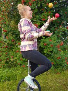 Nainen ajaa yksipyöräisellä ja jongleeraa